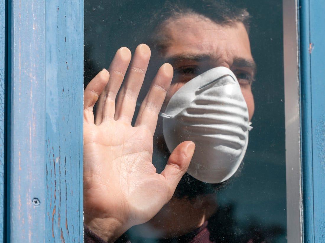 Se ve una persona con mascarilla desesperada por la pandemia, quizá pensando en el suicidio
