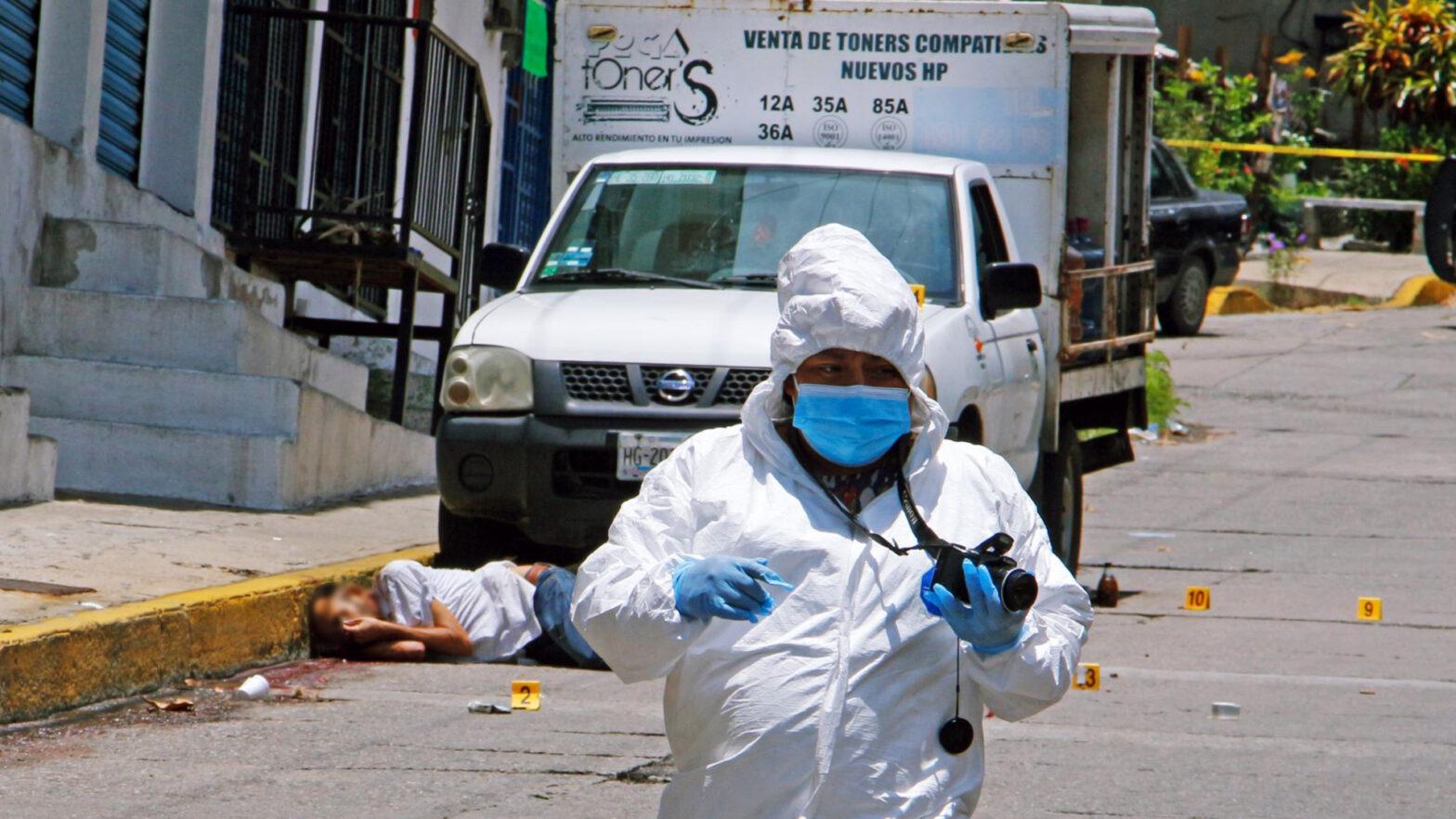 Perito camina frente a una escena de violencia en Mexico