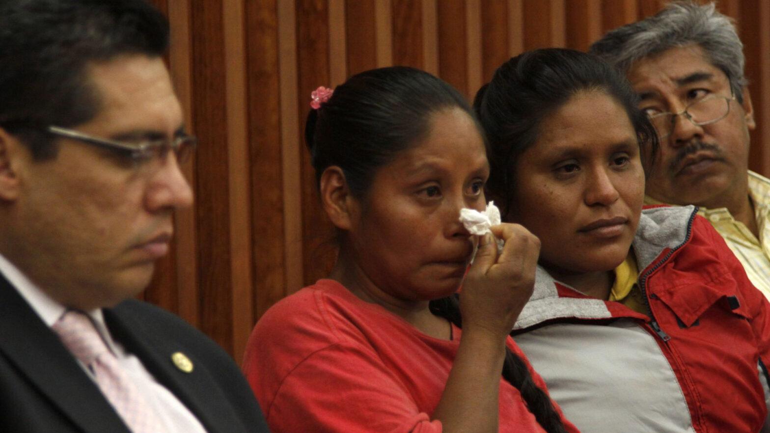 Mujeres indigenas lloran con un pñuelo en la mano