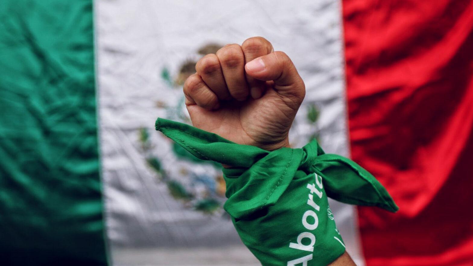 una mano con un pañuelo se levanta delante de la bandera de México en pro del aborto