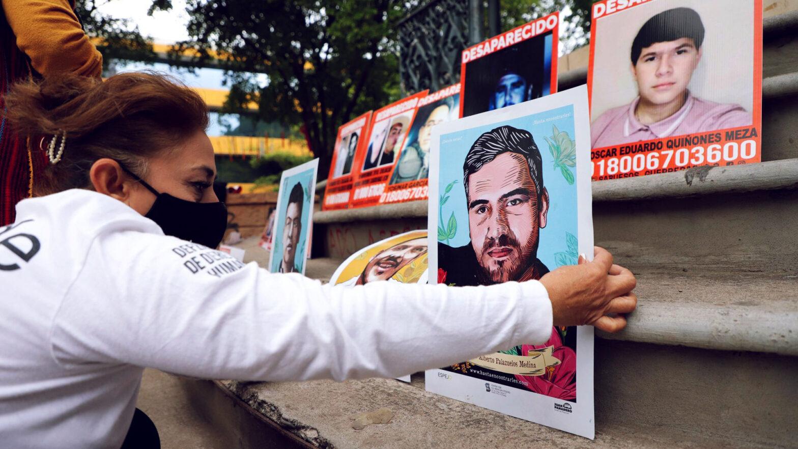 mujer acomoda la foto de un familiar para reclamar en México desaparición de personas