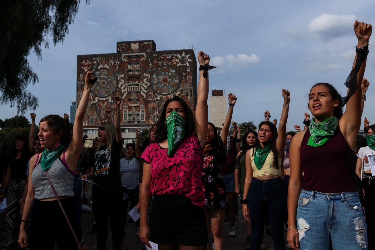 mujeres alzan sus puños en protesta por la violencia de genero en la unam